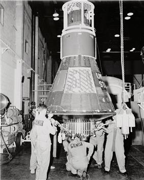 Men in overalls clustered around the base of an upright conical spacecraft, which is two or three times taller than them, inside a large room