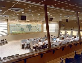 A large room seen through windows at the rear, with two rows of people seated at desks and computers, and a map taking up the whole of the front wall.