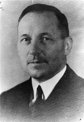 Head of a middle-aged white man with thinning hair, wearing a dark suit coat, white shirt, and dark tie.