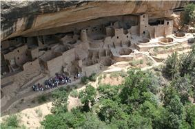 Ruins of circular and rectangular buildings under an overhanging cliff.
