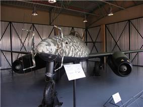 A twin engine jet aircraft pictured from front-left sitting on the ground in a hangar. The paint scheme of the aircraft is camouflage of various brown and green colours. Two antennas are protruding from the nose of the aircraft. The white number