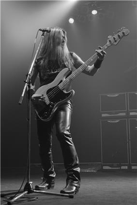 A long-haired man playing bass guitar onstage