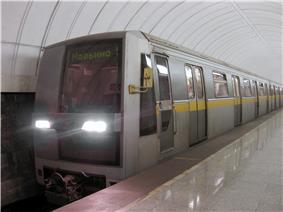 Modern, silver-colored train pulling into a station