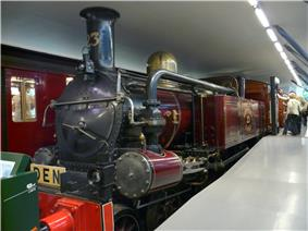 A steam tank locomotive is shown indoors, funnel towards the viewer, in purple livery. A large pipe connects the pistons at the front with the side tank