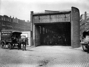 A horse and cart stand in a street outside a narrow building with large open doors and a dark interior. A sign above the doors says