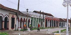 A street with single-storied colonned buildings that are painted in various colors.