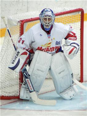 An ice hockey player standing partially crouched in goals. He is wearing a helmet, gloves and leg pads and a white uniform.
