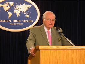 Michael Novak behind a lectern, speaking at the Foreign Press Center in Washington