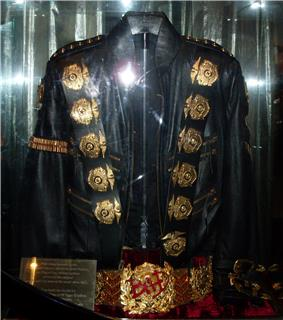 A black jacket with five round golden medals on its left and right shoulders, a gold band on its left arm sleeve, and two belt straps on the right bottom sleeve. Underneath the jacket is a golden belt, with a round ornament in its center.