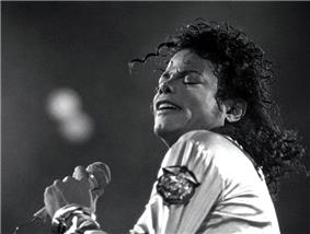 Black and white photo of Jackson holding a microphone and singing.