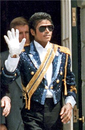 Michael Jackson, an African-American man in his mid-twenties wearing a sequined military style jacket and dark sunglasses. He waves his right hand, which is adorned with a white glove. His left hand is bare.