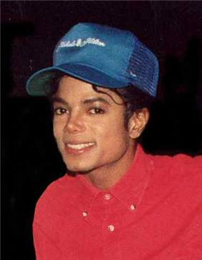 A man in a red shirt smiling toward the camera. Atop his head is a blue baseball cap.