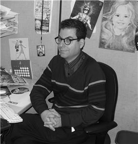Musto seated at a desk