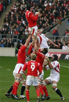 A Welsh player grasping the ball while being held in the air by his team-mates following a line-out