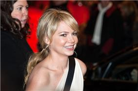 An image of a smiling Caucasian woman. She has her blonde hair in a ponytail and is wearing a one shouldered white dress with a black horizontal stripe.