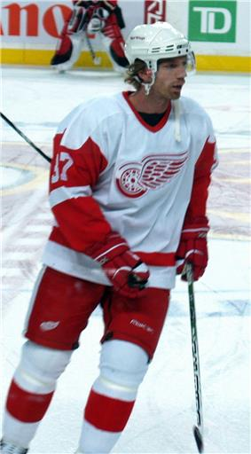 A Caucasian ice hockey player in his thirties. He is skating relaxed on the ice while looking to his right. He wears a white and red jersey, along with a white-visored helmet.