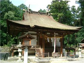 A small wooden building with a roofed, raised veranda with a handrail