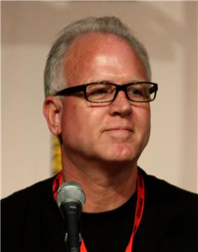 A man with white hair and glasses sits behind a microphone.