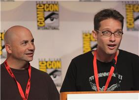 A man with a bald head and a brown sweater, and a man with spiked brown hair and glasses, speaking into a microphone.