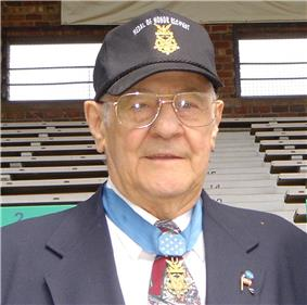 Head and shoulders of an elderly white man wearing glasses and a baseball cap with an image of a star-shaped medal and the words