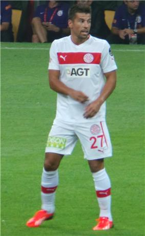 Photograph of a player in a white football kit standing on grass