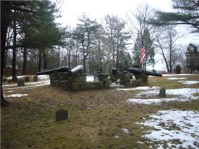 A monument featuring four black cannon barrels mounted on a stone wall in the middle of a small cemetery.  The ground is partly covered with snow.  Many trees stand in the background.  The sky is cloudy.