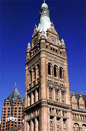 Ground-level view of a large, brick tower with several architectural niches and columns and a tapering, copper roof topped with a spire; a clock are visible on the tower near its roofline.