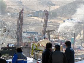 Color photo of San Jose Mine from a distance with several workers in the foreground