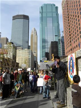 A daytime city scene on a sidewalk with a tall, brick-faced building on the right and glass-covered skyscrapers in the distance in the center. A dark-haired, fairly young man dressed in casual clothes stands next to a drawing of Jesus and speaks through a megaphone. About 25 people of different ages and both genders can be seen watching him, with a few holding signs, one of which says SEIU.