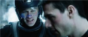 Two men, one of whom is wearing futuristic armor and helmet. A distinctive blue tint colours the image.
