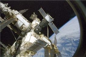 A cluster of modules, covered in white insulation and projecting feathery solar arrays, with a small spacecraft covered in brown insulation docked at their centre. The image is seen through a window, with the blackness of space and the Earth forming the backdrop.