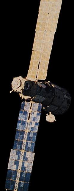 A photograph of a DOS spacecraft. The module consists of a stepped cylinder, with two large solar arrays projecting from opposing sides of the narrower portion of the module. A spherical compartment with five docking ports is attached to the end of the narrower section, whilst a lollipop-shaped antenna projects radially from the far end of the wider section.