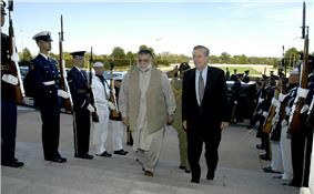 Two men walking between lines of armed soldiers in dress uniforms