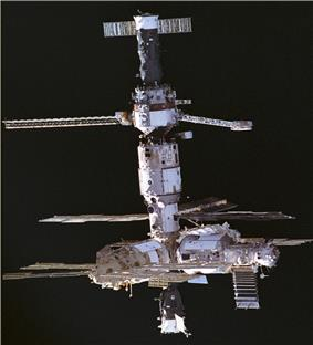 A space station consisting of three white modules arranged in a T shape around a central docking node. A fifth module projects upward from the docking node, with a sixth module attached to its end. A Progress and Soyuz spacecraft are docked to the station, and each of the modules projects various feathery solar arrays, antennas and trusses. The blackness of space forms the backdrop to the image.