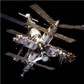 An image of the Mir space station consisting of four modules (the rightmost one with a smaller orange module attached to its distal end) arranged in a cross shape about a central docking node. A sixth module projects rearward from this node, and has a seventh, smaller module attached to the far end. A Soyuz spacecraft is docked at the end of this stack. Each of the modules is projecting various feathery solar arrays, antennas and trusses, and the blackness of space forms the backdrop to the image.