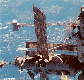 A partial view of a space station, with two modules visible. The vertically aligned module has a large, dish-shaped antenna projecting from it, and a large truss can be seen horizontally behind it, with a white box-shaped device mounted to the end. The horizontal module has a smaller truss mounted to the end of it, with a white backpack attached to this. The module also features two large solar arrays and a number of cameras mounted to a unit on the distal end of it. Another solar array is visible behind this module.