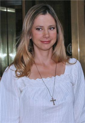 Profile of a blonde woman who is wearing a religious necklace over a white dress.