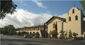 Photograph of Mission Santa Inés, showing the campanile on the right, the chapel at center, and the long, colonnaded walkway to the left.