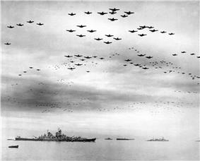 Black and white photo showing a large number of aircraft flying in formation over several World War II-era warships