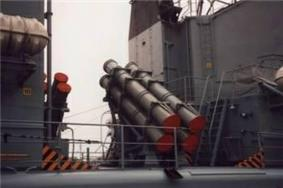 A Quartet of grey colored cylindrical canisters positioned roughly in the center of the image, with the canisters pointed at angle with the base to the lower right. A clear space can be seen in the left third of the image.