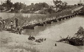 A low bridge over twelve pontoons, with troops on the nearby bank