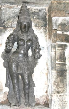 A stone carving of a standing woman with a pot in her left hand and lotus in right.