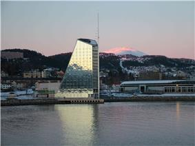Multi-storied glass building in the shape of a gaff-rigged sail.