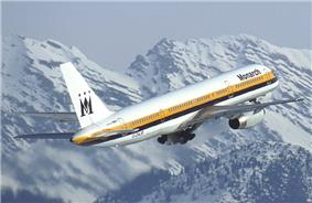 Side quarter view of aircraft at takeoff, with snow-covered mountains behind.