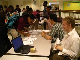Two young white men sit at a table with several teenage African American students mingle around it, and one signs a paper on it. Also on the table is a laptop.