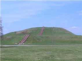 Large grassy mound. A flight of steps leads to the top of the mound.