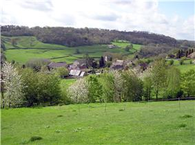 The roofs of houses and farm buildings in a green valley. Trees in the foreground