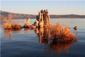 A rock formation rises from the surface of a calm lake.  Plantlife appears to grow from around the rocks.  In the distance, the horizon is filled with steep hills and small mountains.  The sky is blue, and the sun appears to be low, casting long shadows across the image.  The rocks and plant life appear sandy in colour.