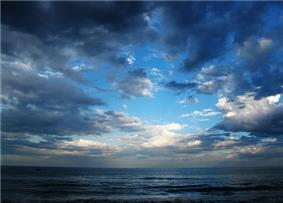 Late daytime view looking far out over an ocean from a beach, which is out of view off the bottom margin. Three-fourths of the shot features a sky marked by heavy cloud cover, which is parting near the middle, revealing a dazzlingly bright cerulean blue sky that darkens near the margins. The ocean is striated with waves coming in parallel to the horizon.