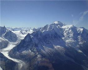 Photograph of a towering snow-covered mountain at right, a glacier at left, and a clear blue sky.